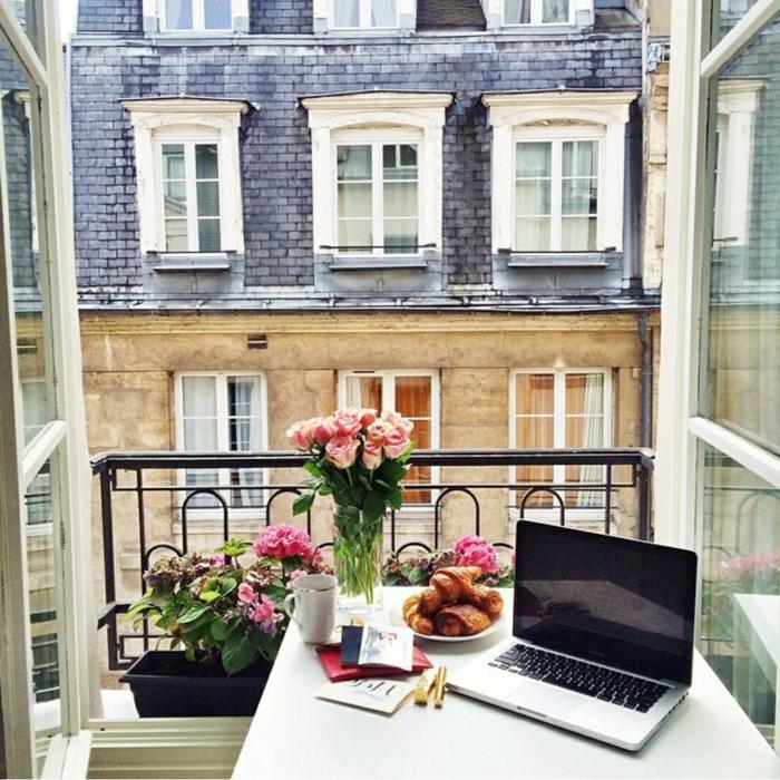 Laptop auf einem Tisch mit pinken Blumen, Ikea Balkon Ideen, offene Fenster, Croissant in einem Teller,