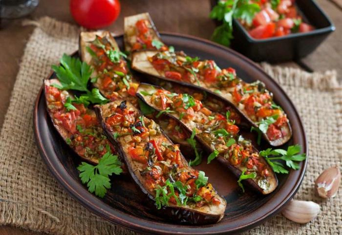 Auberginen Pizzen mit Tomaten auf einem schwarzen Teller, leichte vegane Rezepte für Anfänger, lecker Gericht des Tages