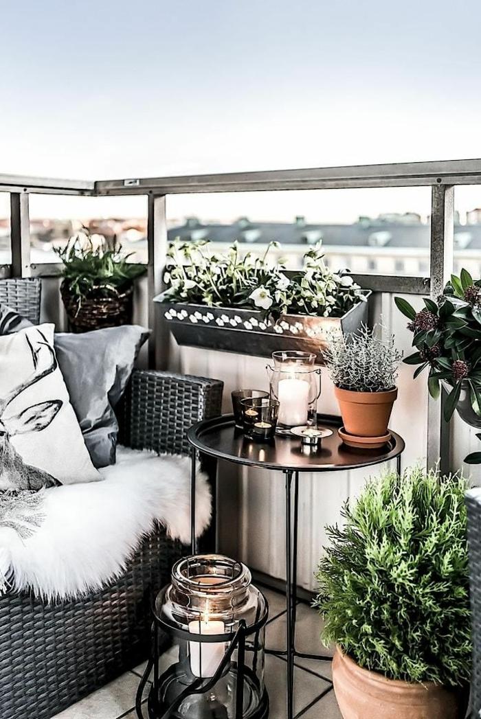 Möbel für kleinen Balkon, kleiner runder Tisch, graues Sofa mit Kissen und flauschiger Deke, grüne Pflanzen und Blumen