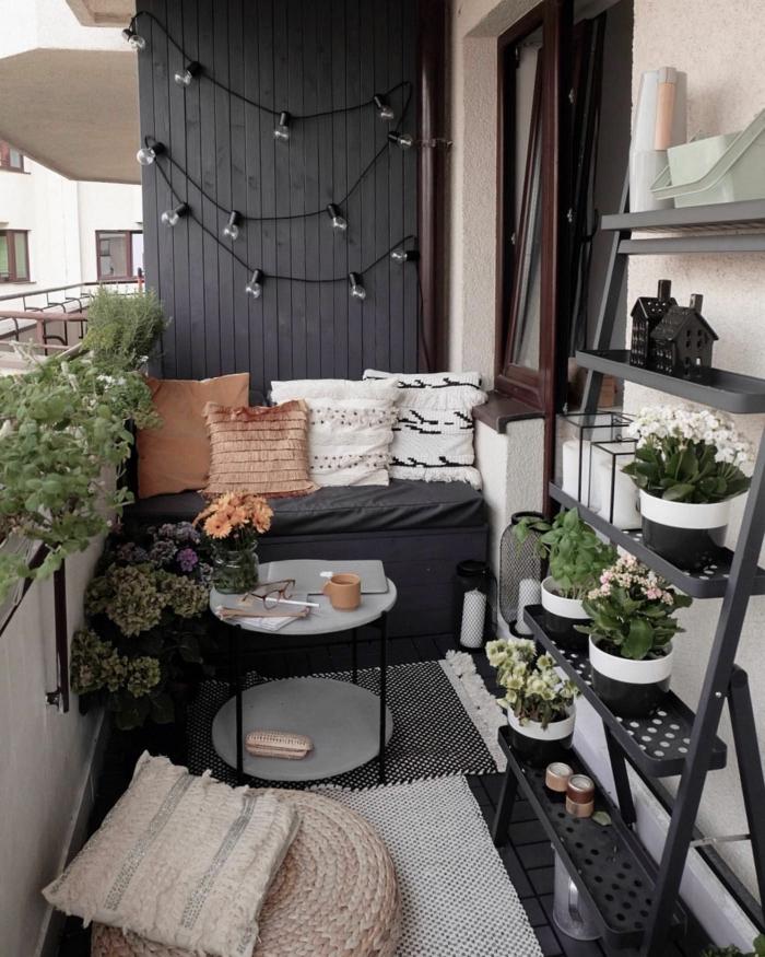 Balkon Lounge klein, schwarze Wand mit aufgehängten Hängeläuchter. Pflanzenständer mit vielen Pflanzen, kleiner grauer Sofa mit Kisse