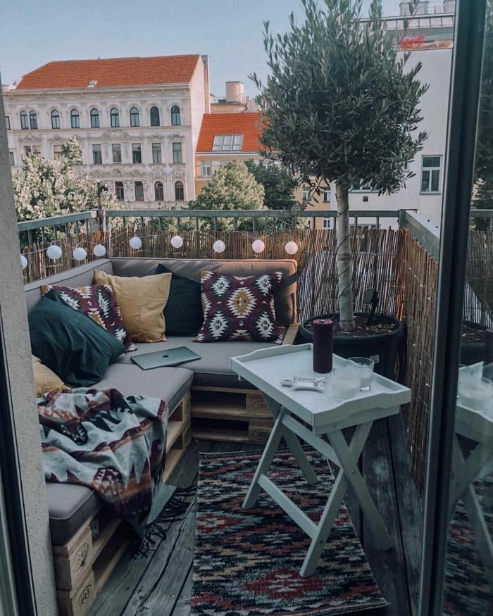 kleiner Balkon Inspiration, Ecksofa aus upcyclete Kisten, bunte und gelbe Kissen, großer deko Baum, kleiner Frühstückstisch