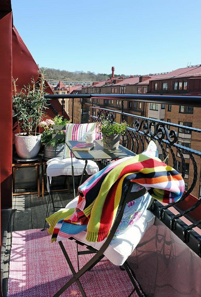 Möbel für kleinen Balkon, bunte Decke auf einem Stuhl, pinker Teppich, rote Wand, Dekoration für Terrasse