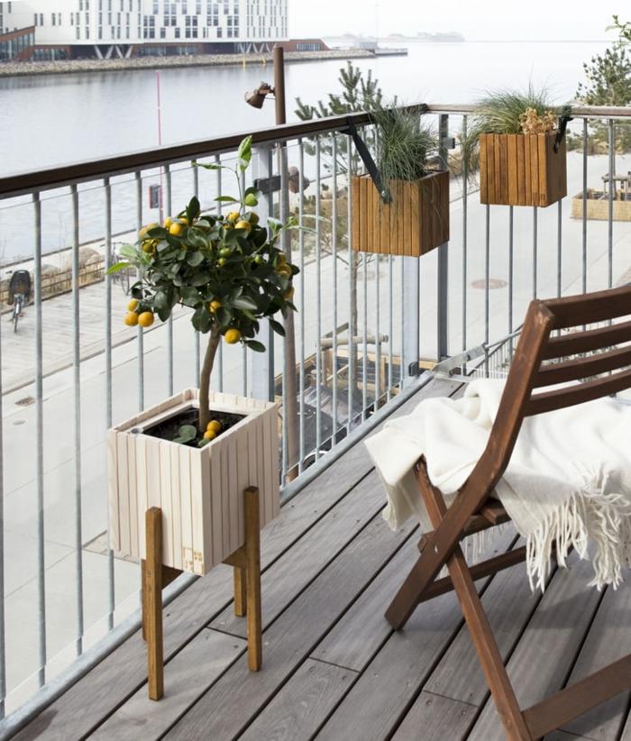 Balkon gestalten Ideen, Stuhl aus Holz mit einer weißen Decke obendrauf, kleiner Zitronenbaum, Aussicht zum Fluss