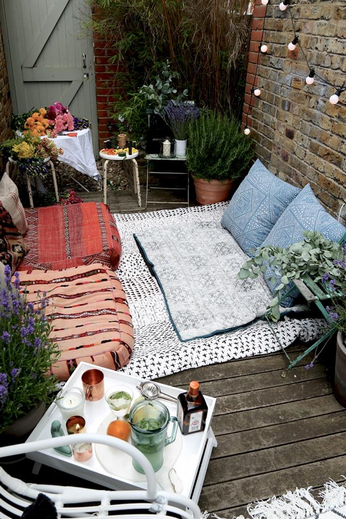 Backsteinwand mit aufgehängten Läuchter, Bodeck bedeckt mit Teppich zum liegen und blaue Kissen, Deko für Garten und Terrasse