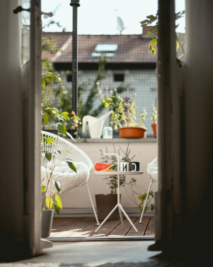 Möbel für kleinen Balkon, Dekoration mit Terrassenpflanzen, kleiner dreibeiniger Tisch, Stück Wassermelone