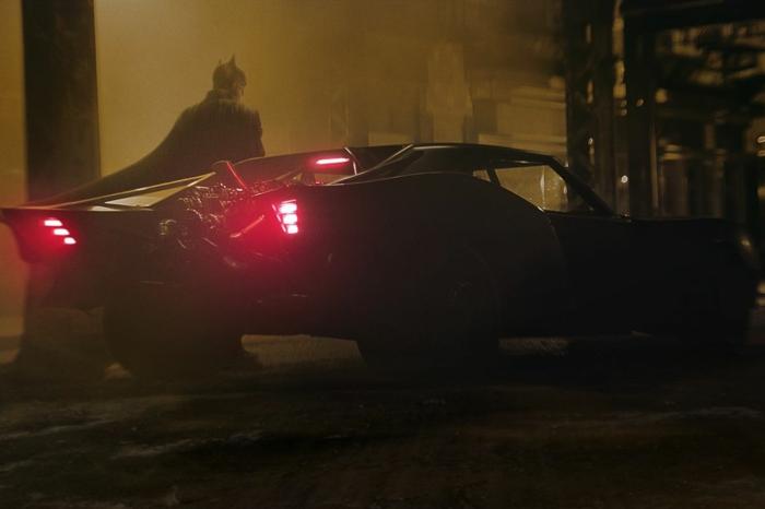 der schauspieler robert pattinson in einem schwarzen kostüm, scwarzes auto batmobil, the batman von matt reeves
