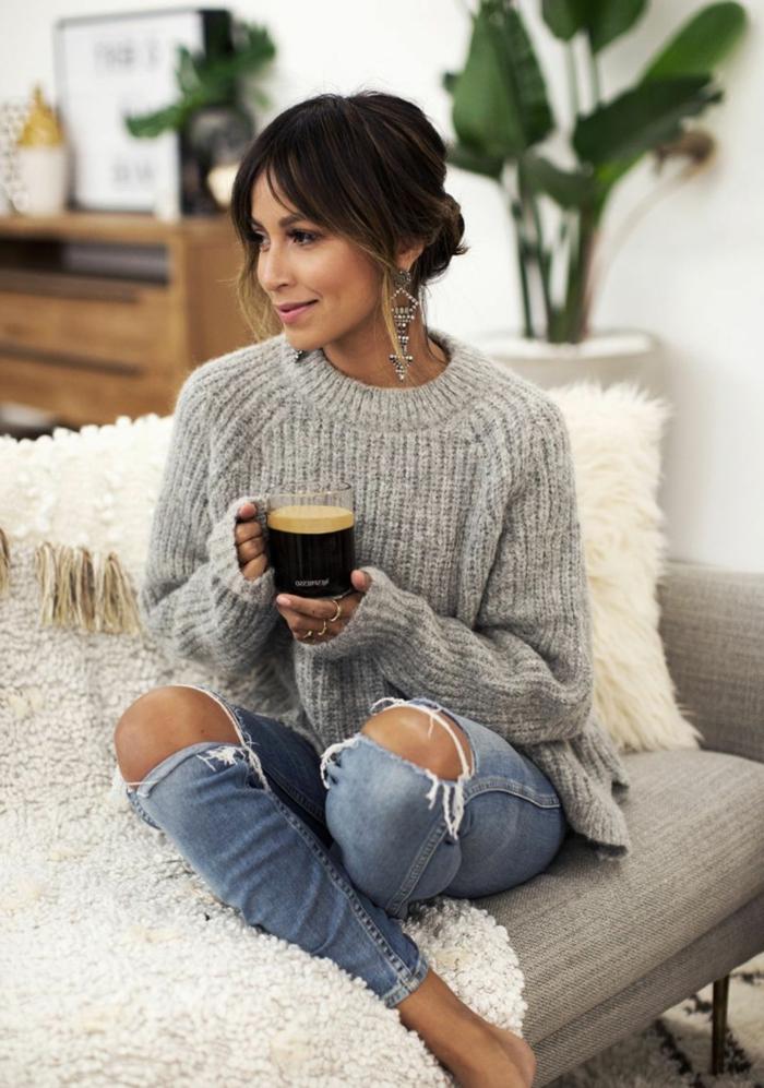 lässig gekleidete Frau im kuscheligen Pullover und gerippten Jeans, hält eine Tasse Kaffee, hochgesteckte Haare, pony styles