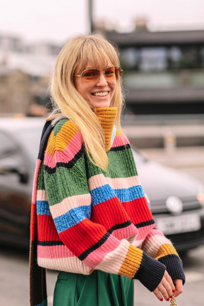 Frisuren mit Pony 2020, lässig und stylisch angezogene Frau mit weitem farbigem Pullover und grüne Hose, blonde lange Haare mit Pony