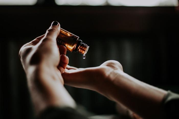 CBD Öl, Anwendungsbereiche des Öls, Hand hält eine CBD Flasche und tröpfelt CBD auf die Handfläche