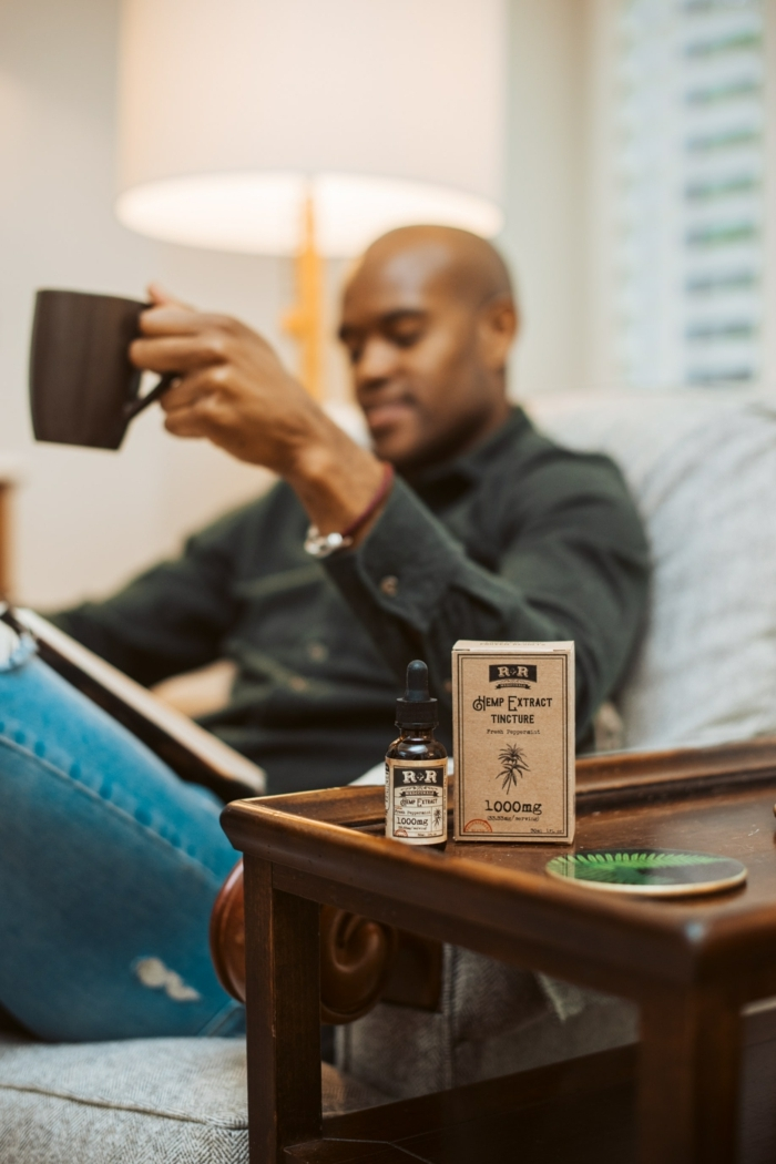 CBD Öl Anwendungsbereich, Anwendungsbereiche und Heilung von Leiden, Mann hält eine Tasse, kleine CBD Flasche