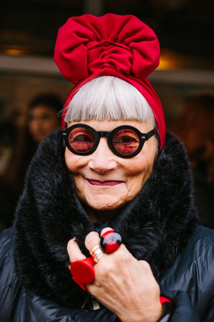 eindrucksvoll gekleidete ältere Dame, runde rote Sonnenbrillen und große Ringe. weiße Haare, micro Pony, effektvoller Hut