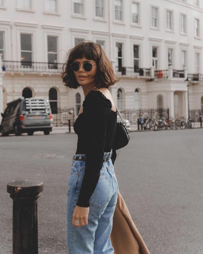 Lässig gekleidete Frau in Jeans und schwarze rückenfreie Bluse, brauner Mantel, runde Sonnenbrillen, Kurzhaarfrisuren mit Pony,