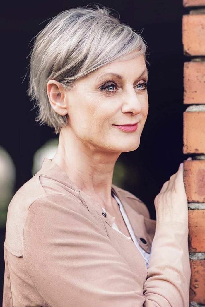 gestufter bob für ältere frauen, dame mit grauen haaren, leicht geschminktes gesicht, hellbraune bluse, frisuren mit pony