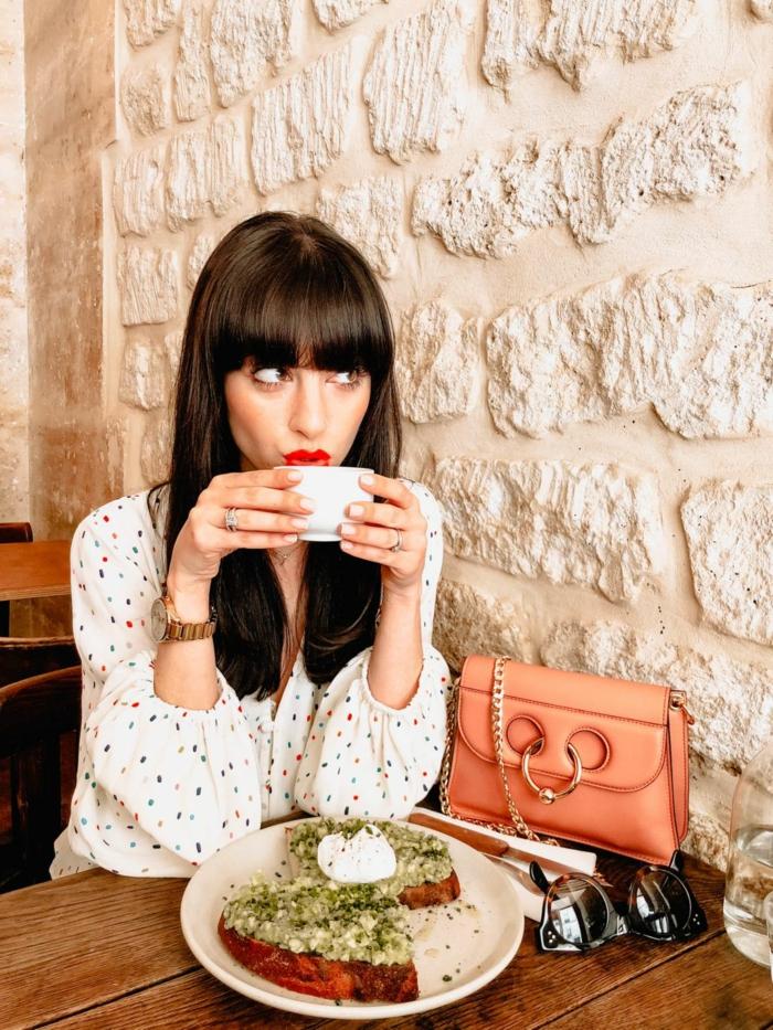 Frau trinkt Tee, kleine braune Ledertasche, Schulterlange Haare mit Pony, weißes Hemd mit Pünktchen, Avocado Toast auf dem Tisch, Frisuren mit Pony 2020