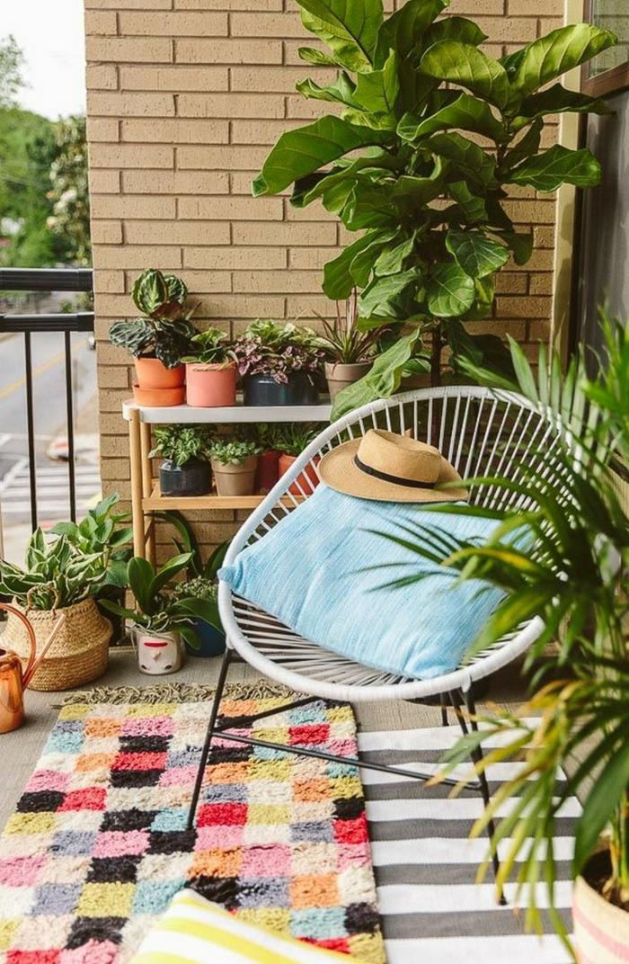 Balkon gestalten Ideen, Ständer mit vielen Pflanzen, moderner Stuhl mit einem blauen Kissen