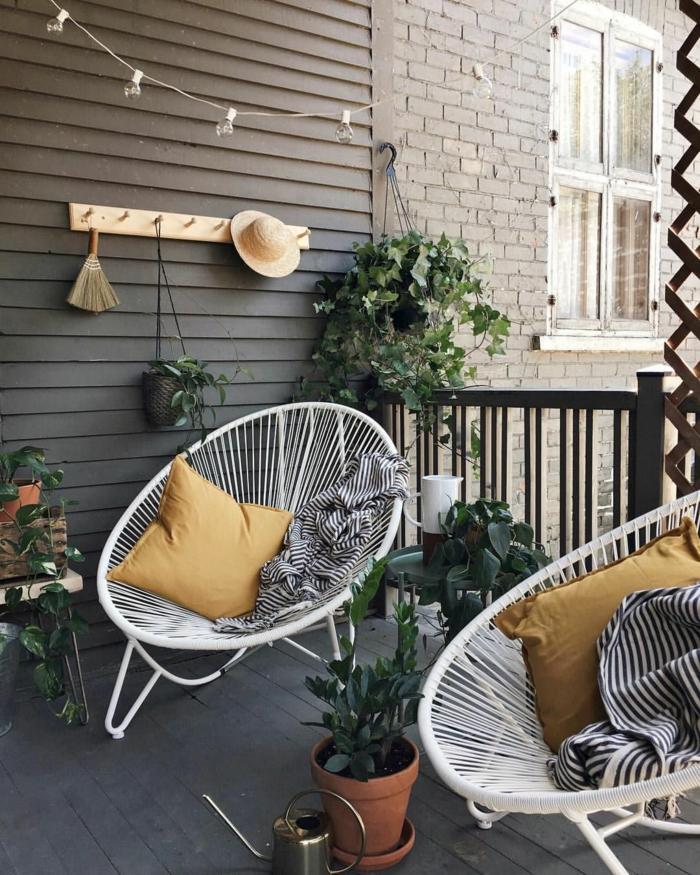 zwei weiße Stühle und gelbe Kissen, Möbel für kleinen Balkon, aufgehängte grüne Pflanze, schwarz weiße Decken