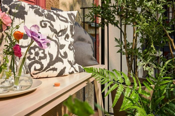 Deko für Garten und Terrasse, schwarz weißer und grauer Kissen, grünes Gewächs, Blumen in Vasen