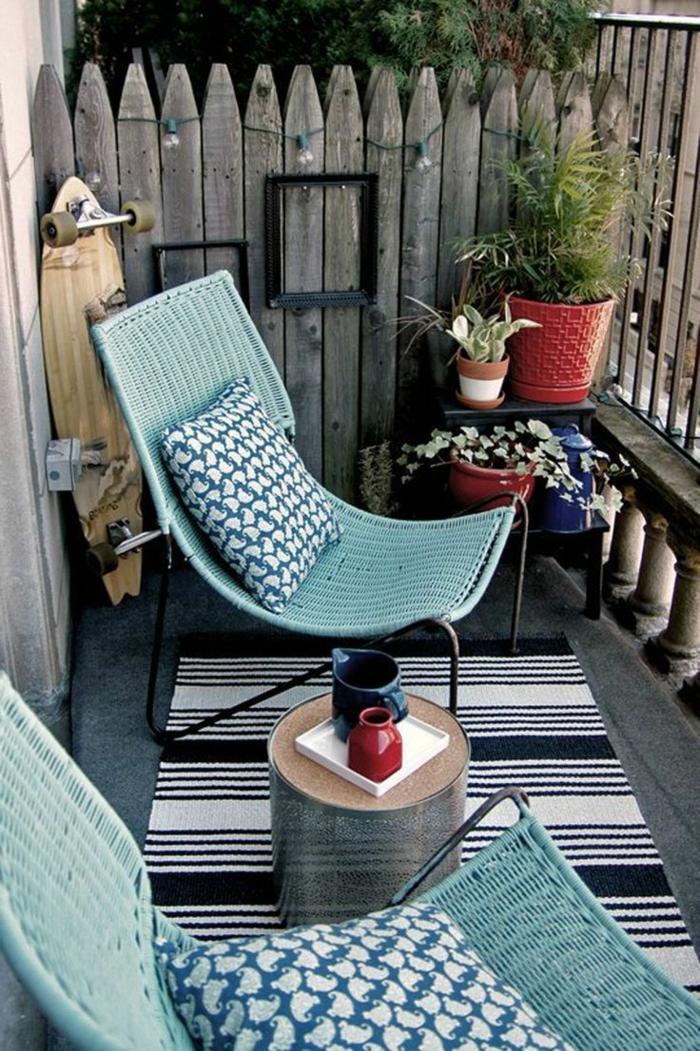 Ikea Balkon mit zwei Liegestühle in blauer Farbe und mit Kissen, Blumentöpfe mit Pflanzen, schwarz weißer Teppich