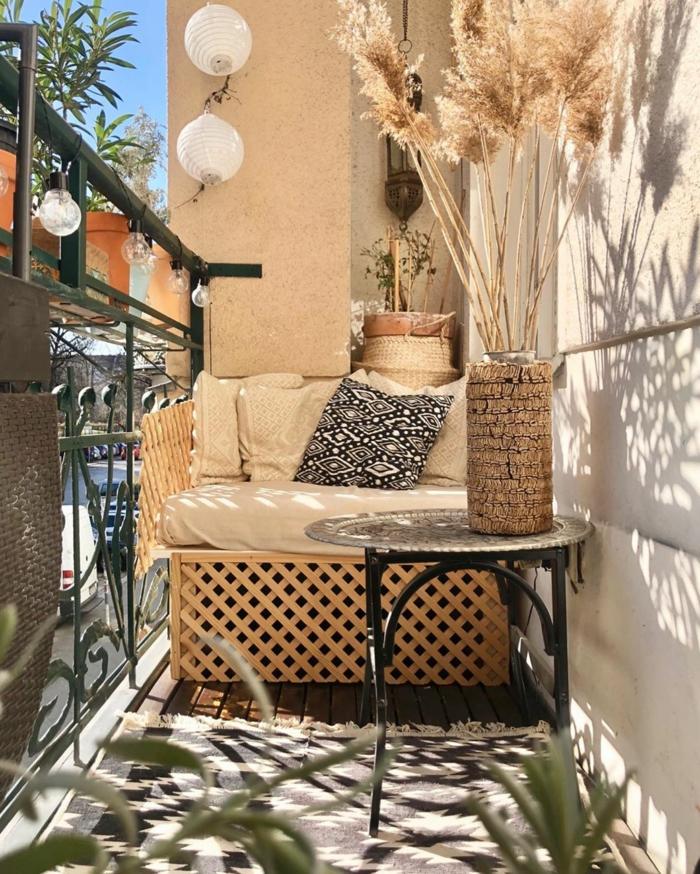 Eingerichtete Terrasse in hellen Farben, Balkonmöbel Set für kleinen Balkon, aufgehängte Lampen, schwarz weißer Teppich