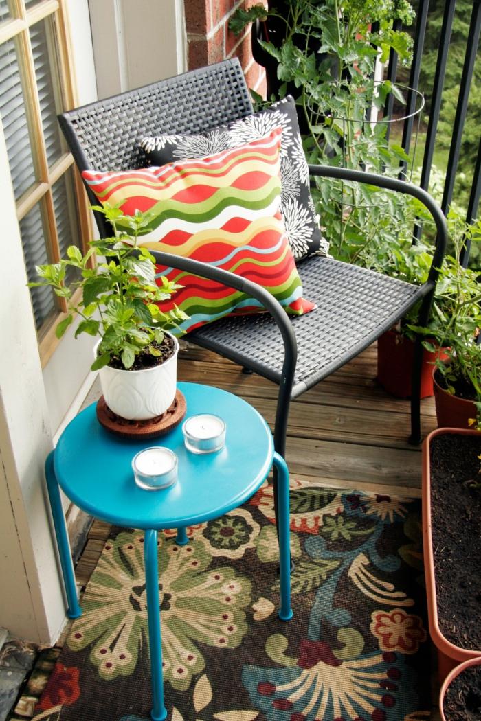 gemütlich gestalteter kleiner Balkon, schwarzer Stuhl mit einem bunten Kissen, runder blauer Tiscg, Teppich mit Blumen Motiven, Deko für Garten und Terrasse