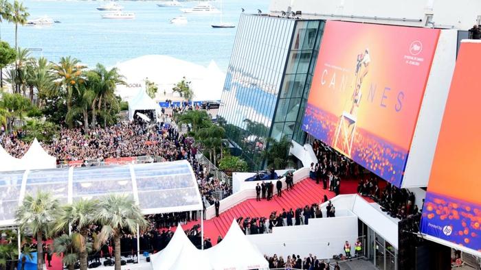 viele menschen und palmen, poster zu den internationalen filmfestspielen von cannes, coronavirus