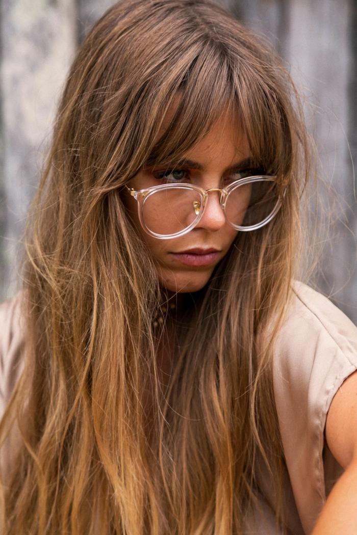 Frau mit braunen mit dunkelblonden langen Haare, große und runde Brillen, curtain bangs trend 2020, pony styles