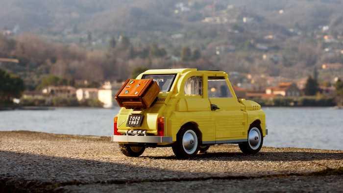 das neue gelbe auto fiat 500, ein wagen aus kleinen gelben lego ziegeln, see und auto mit braunem koffer