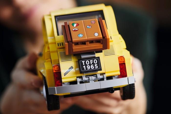 fiat 500 lego creator expert, hände und ein spielzeug mit braunem koffer mit der fahne von italien