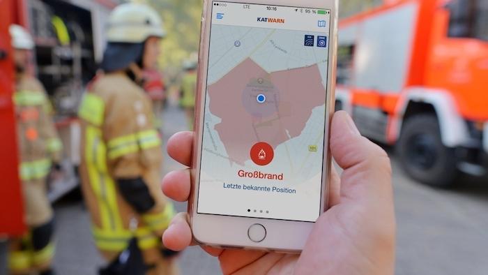 feuerwehr und eine hand mit smartphone mit der kostenlosen anwendung katwarn