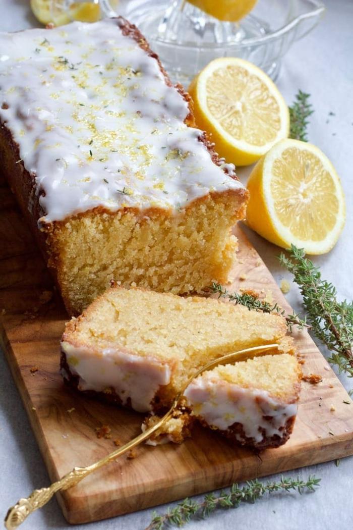 veganer Brunch Rezepte, Zitronen kuchen mit Zuckerguss auf einem hölzernen Brett, ein aufgeschnittenes Stück Kuchen
