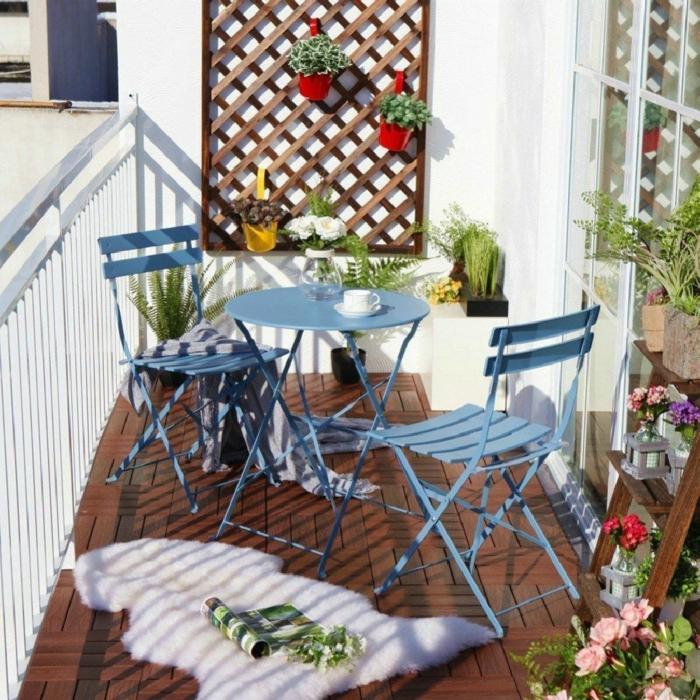 Balkonmöbel Set für kleinen Balkon in blauer Farbe, weißer flauschiger Teppich, Pflanzenständer mit vielen Pflanzen