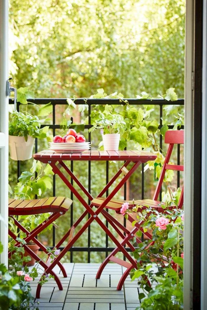 Cozy Gestaltung einer Terrasse, Möbel für kleinen Balkon, zwei Stühle und Tisch in roter Farbe, Äpfel in einem Teller