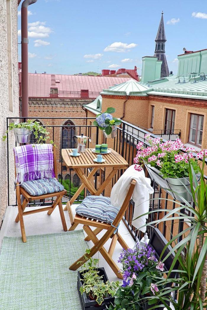 zwei Kaffeetassen und Kaffeekocher auf einem Holztisch, zwei klappbare Stühle, Balkon Inspiration