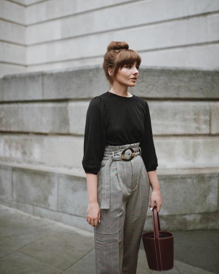 Elegant gestylte Frau, Hose mit hocher Taille, weite schwarze Bluse, pony styles, hochgesteckte Frisur im Dutt