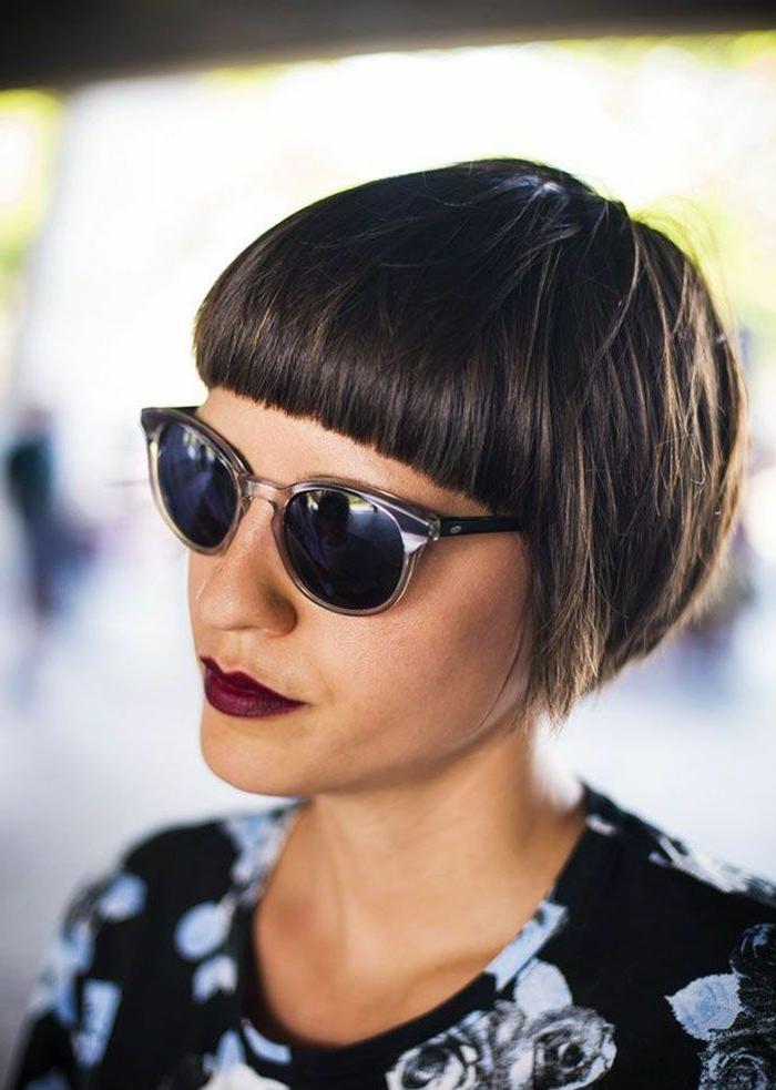 sehr kurzer haarschnitt, frau mit dunklen Haaren, schwarze Bluse mit blumenmotiven, runde Sonnenbrillen, kurzhaarfrisuren mit pony