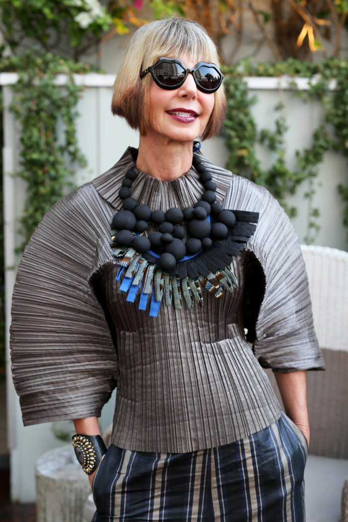 gestufter bob für älter frauen, stylische dame, geometrische schwarze sonnenbrillen, voluminöse halskette und bluse in grau