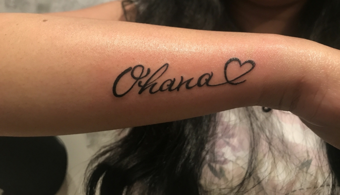 familien tattoo am oberarm, balckwork tätowierung mit ohana und herzen als motiv