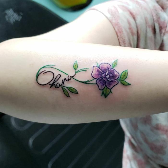 familien tattoo ideen, farbige tätowierung mit blume und unendlichkeitszeichen am unterarm, ohana