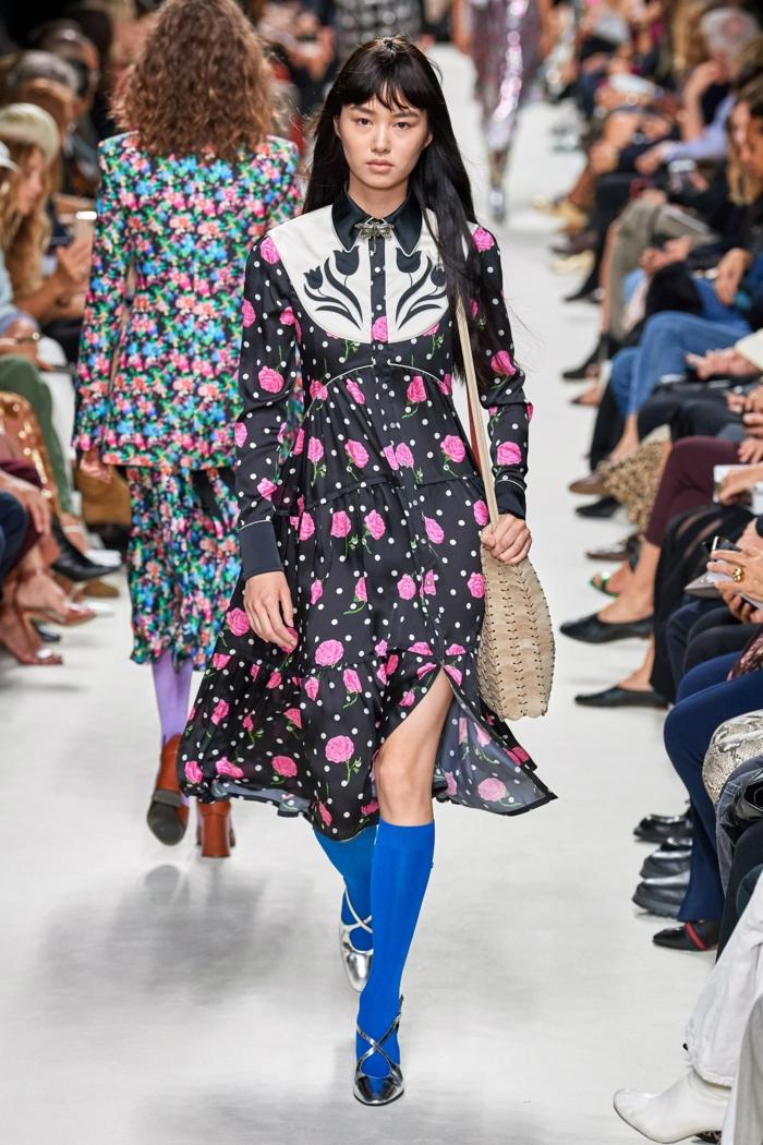 Pacco Rabbane Fashion Show Frühling 2020, langes schwarzes Kleid mit pinken Rosen, blaue Socken, Model mit schwarzen Haaren, pony styles