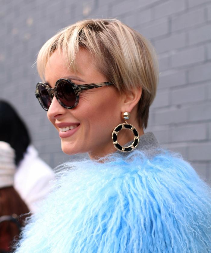 kurzhaarfrisuren mit pony, elegante frau in blaue flauschige, große Ohrringe, blonde kurze Haare, street style