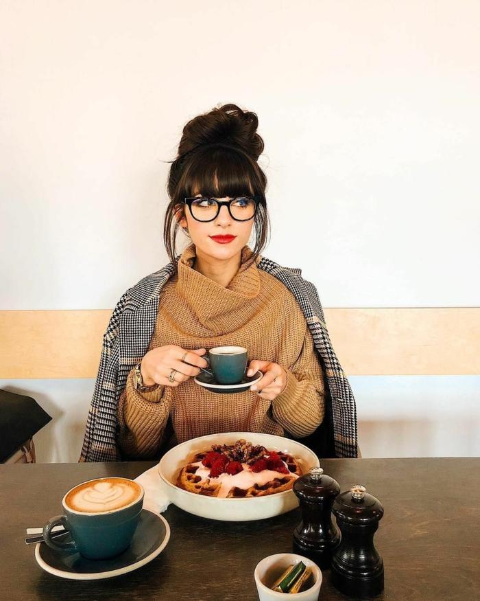 Frau mit Brillen trinkt Cafe in einem Kaffee, Frau mit dunkeln Haaren und Hochsteckfrisur, frisuren mit pony 2020, braunes Rollkragenpullover