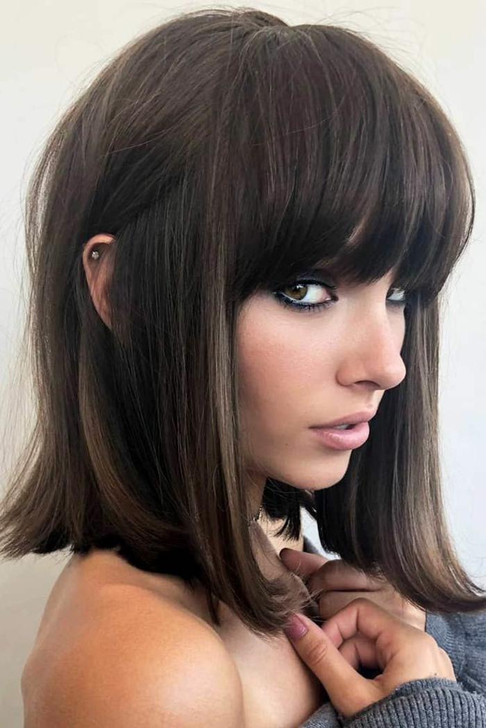 Frau mit dichten braunen Haaren, Pony bei rundem Gesicht, grauer Pullover, kleiner Ohrenpiercing, glatte Frisur