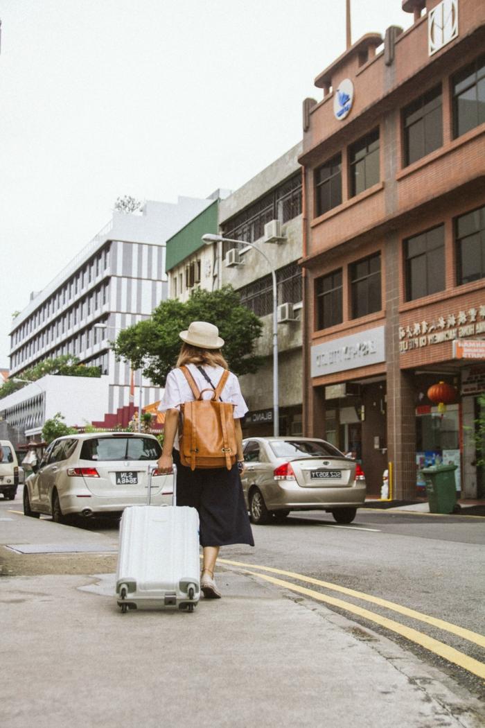 Frau mit einem schwarzen Rock und weißes T-Shirt, zieht einen kleinen Handgepäck Koffer, brauner Rucksack aus Leder, Reisegepäck wählen