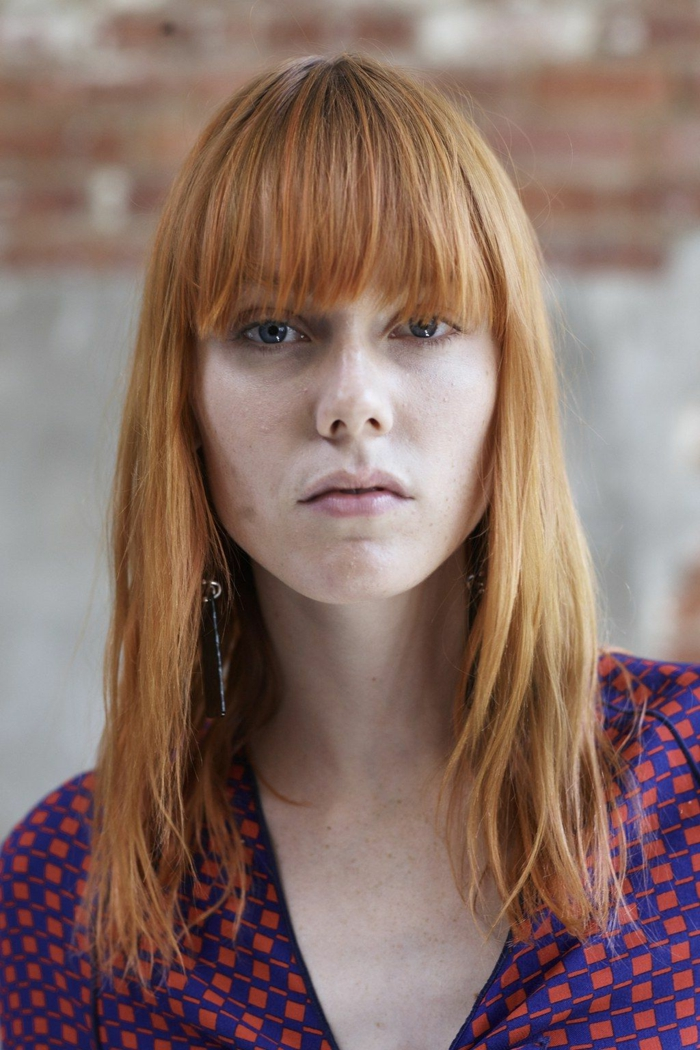 Dame mit glatten rotten Haaren, Schulterlange Haare mit Pony, elegante Bluse in blaue und rote rechtecken