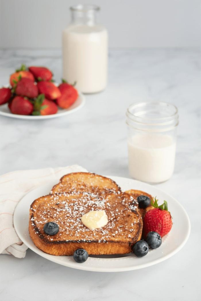 vegane Rezepte für french toast, bestreut mit Puderzucker, mit Erdbeeren und Blaubeeren, veganer Brunch Rezepte