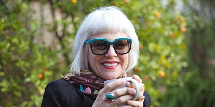 dame mit weißen Haaren, gekleidet in schwarze Bluse und buntem Schal, grüner Ring, gestufter bob für ältere Frauen