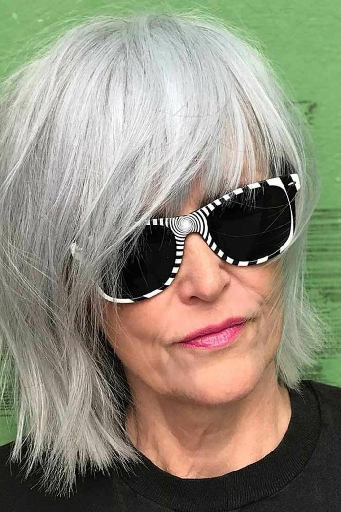 gestufter bob für ältere Frauen, dame mit grauen Haaren, schwarz weiße Sonnenbrillen, schwarze Bluse,