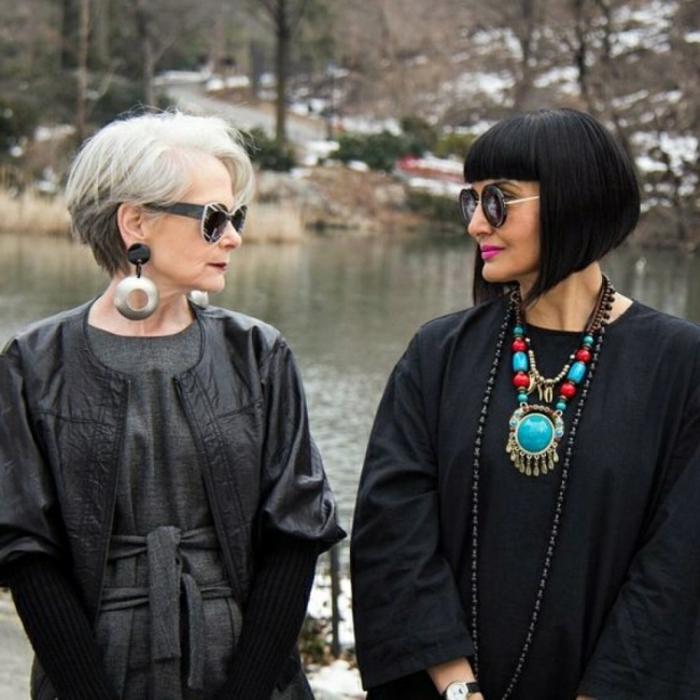 zwei elegante damen in schwarzen outfits, frisuren mittellang stufig mit pony ab 50, auffällige Halsketten