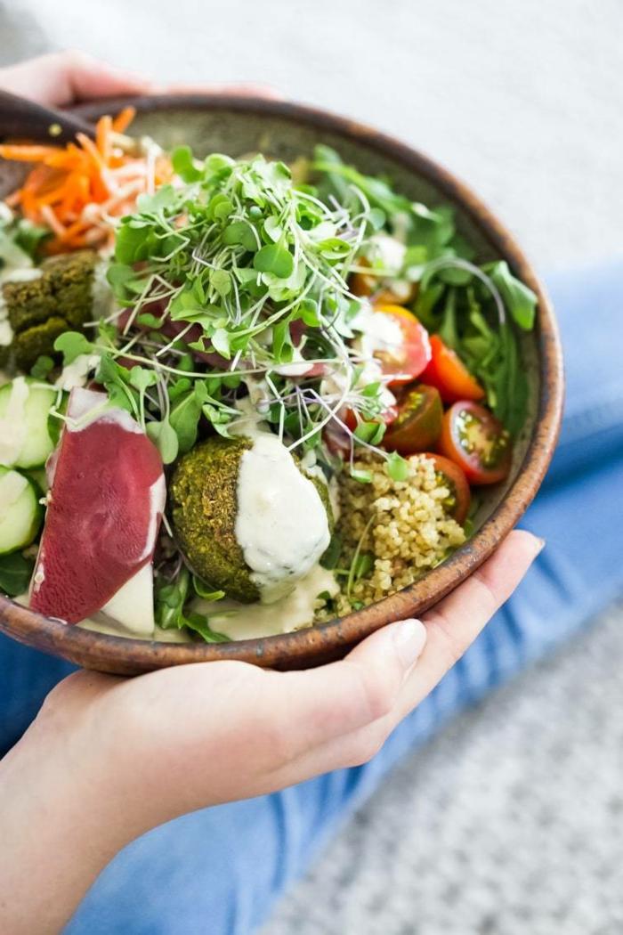 Schnelle vegane Rezepte, Salat mit Falafel Quinoa Cherry Tomaten und Gurken, sättigende Gerichte, Hände halten eine große Bowl