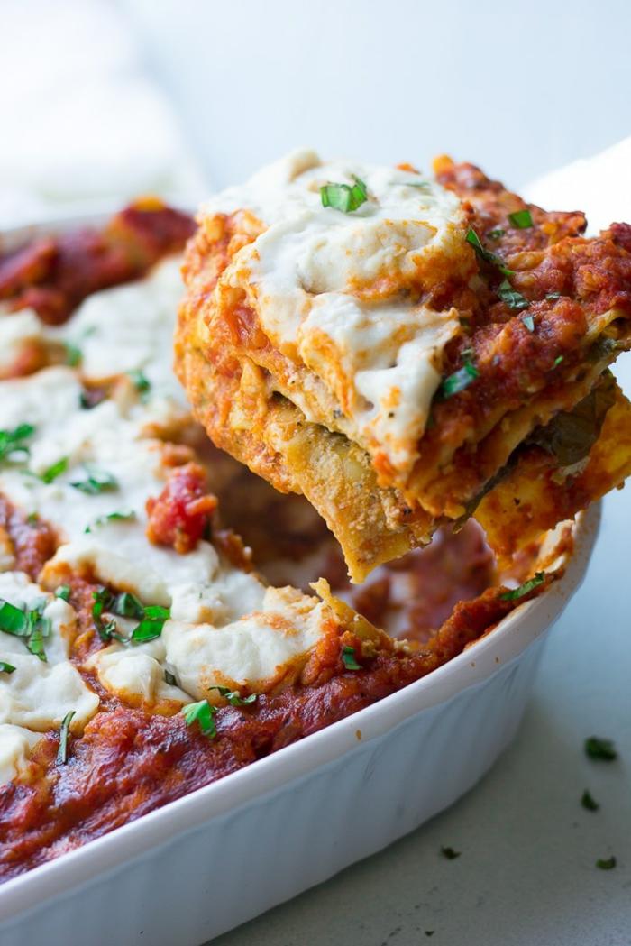 Schnelle Gerichte für jeden Tag, vegane Rezepte für Lasagne mit roten Linsen, Hand schneidet ein Stück Lasagne